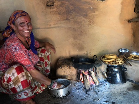 Mrs. Subedi giving a cooking lesson in her kitchen: how to make cell rotis on open fire.