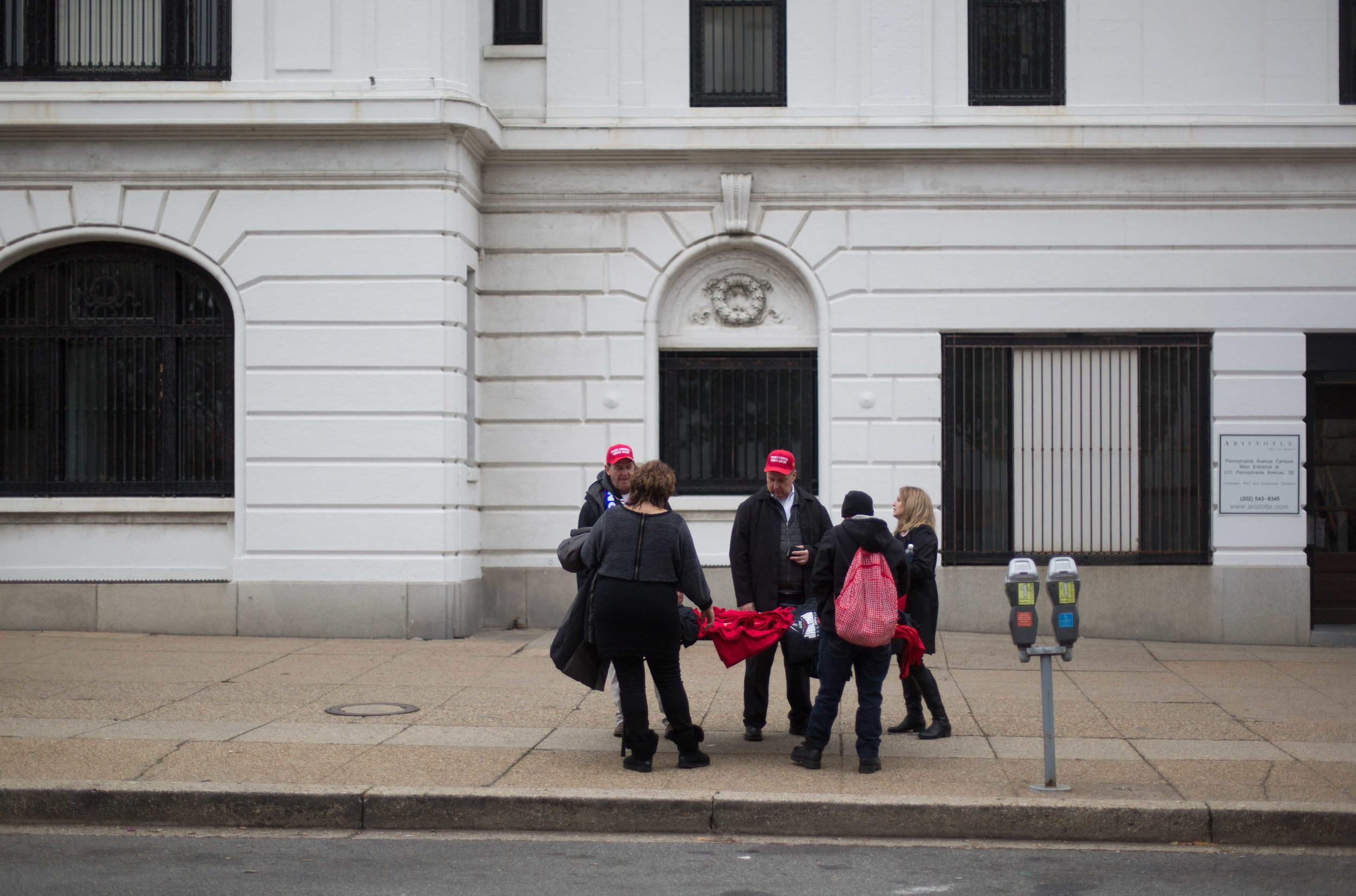 """Another deserted scene, right off the inauguration route - three supporters buy Trump merchandise from a street vendor. One of the supporters laughed about the origin of the garments with me and Rachel, thinking we were Pro-Trump, saying, """"Everything's from Mexico - can you believe it??"""""""