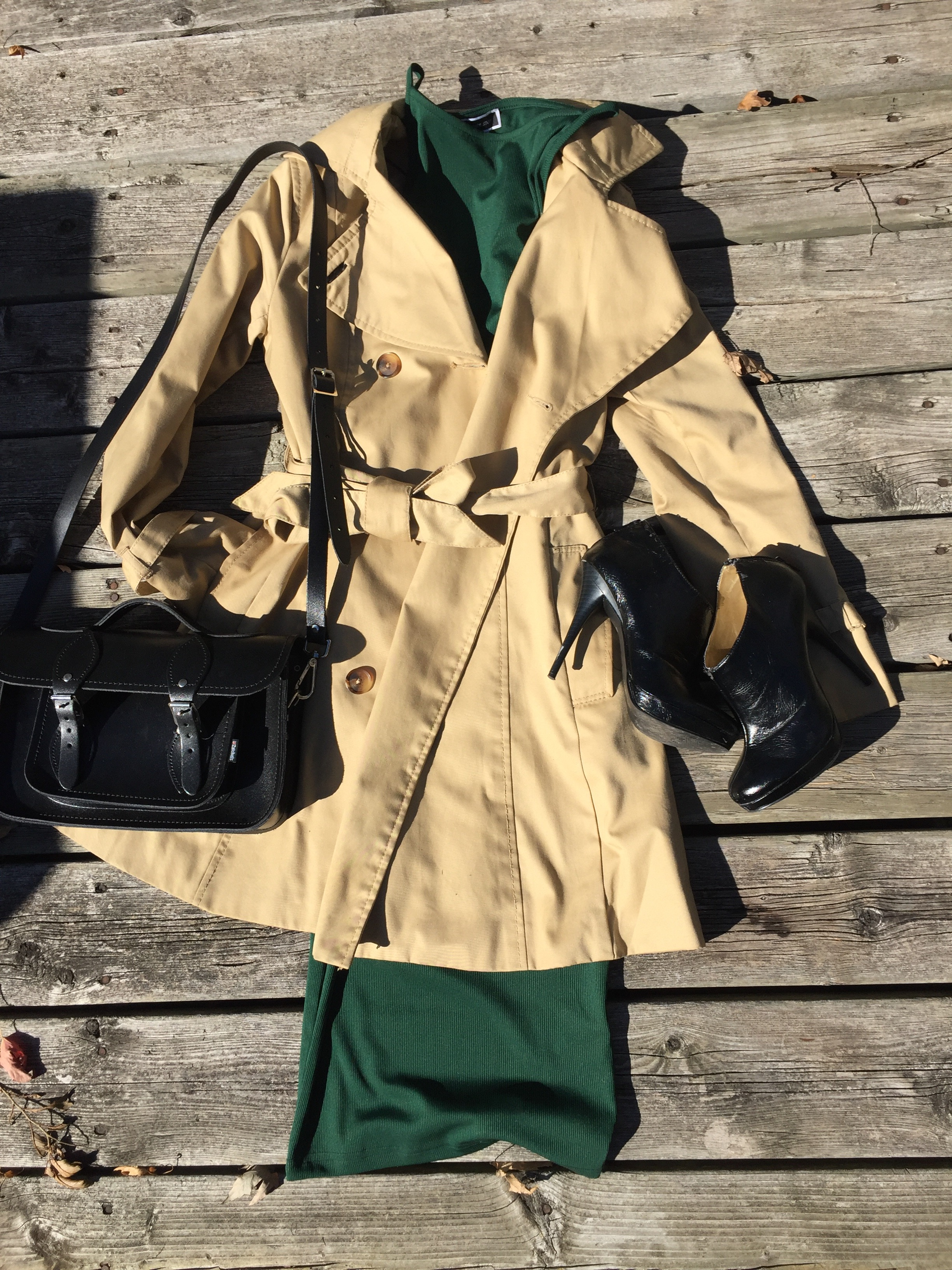 Green midi dress with flared  tan trench coat, black booties and black hand bag