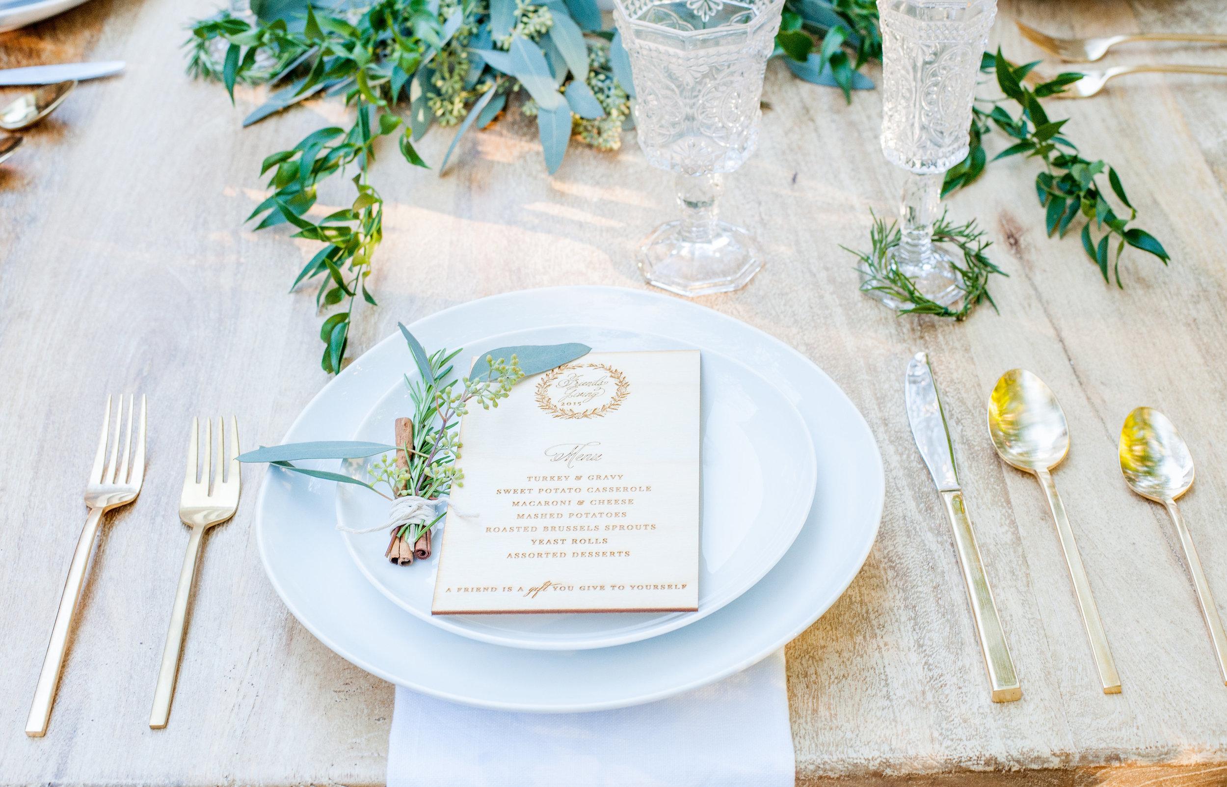 Thanksgivingdecor-Friendsgivingstyledshoot-outdoorliving-goldsilverware-foliage-cinnamon.jpg