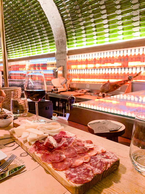 Enjoying a beautiful glass of red Portuguese wine and a charcuterie of meat and cheese from By The Wine in Lisbon
