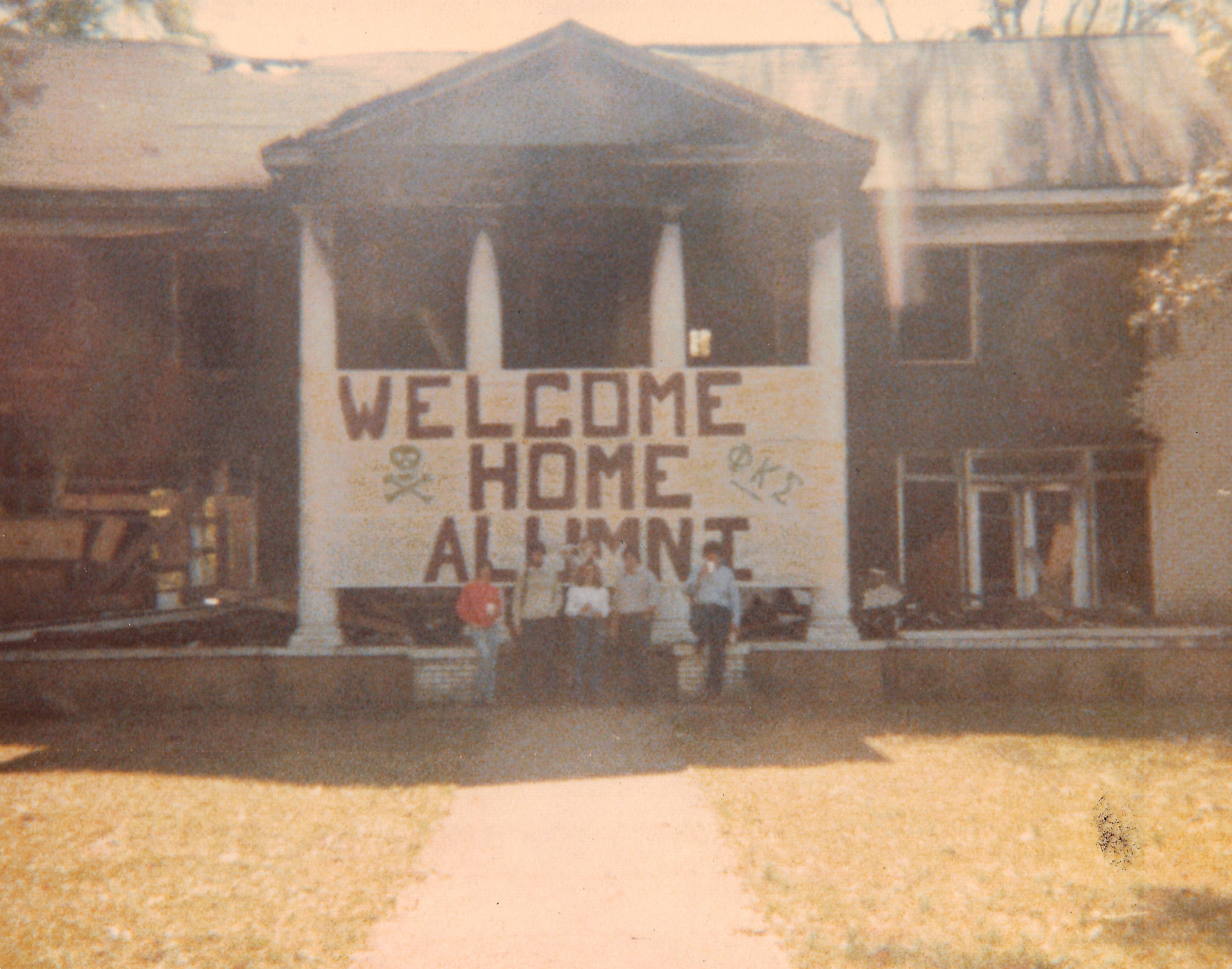 Actives welcoming alumni in front of the charred Chapter house after the Fire of 1979