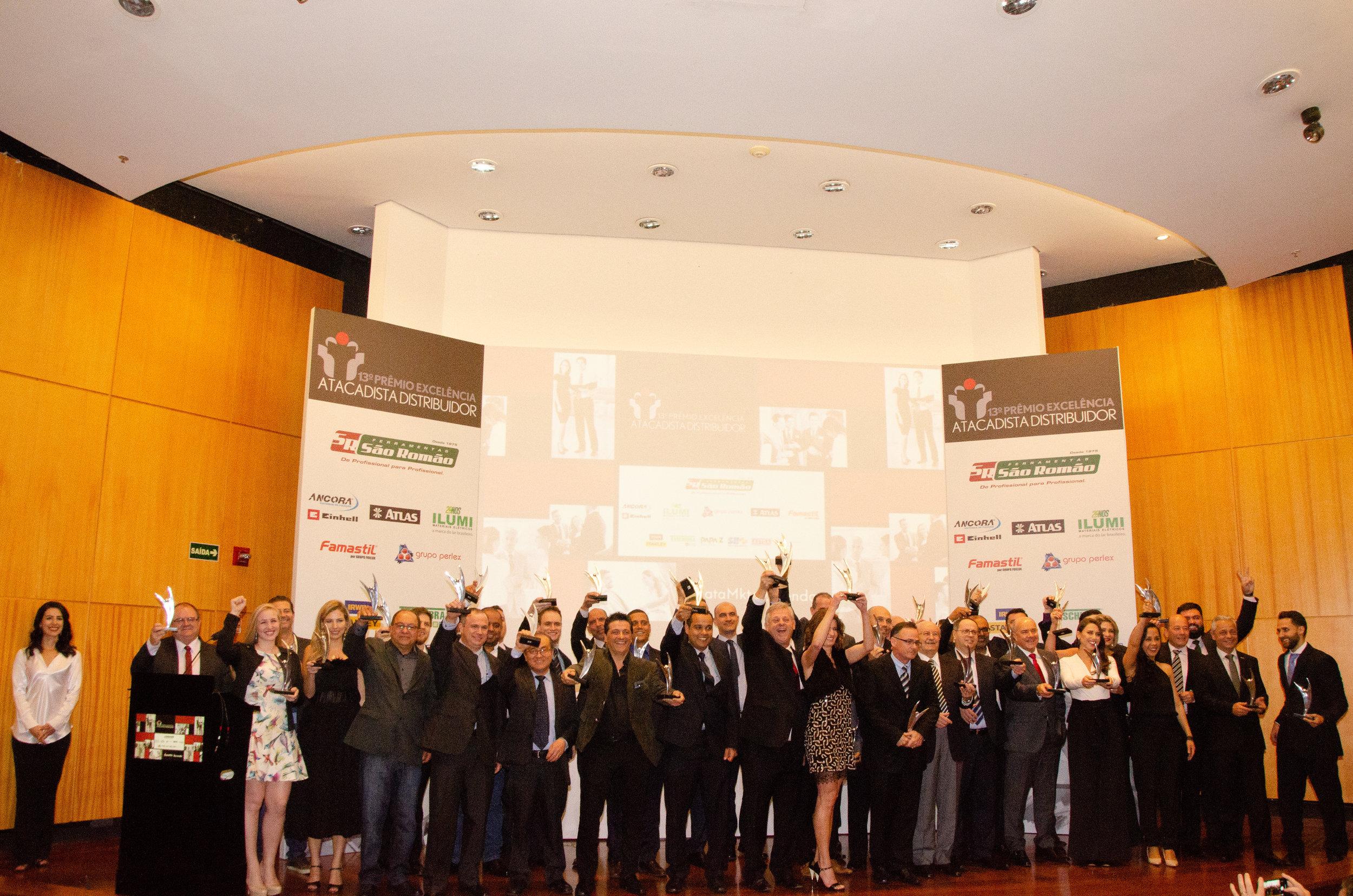 Representantes das empresas comemoram com o troféu