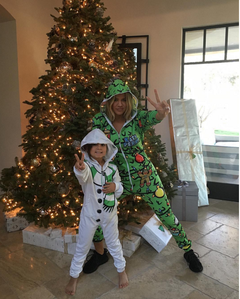 Khloe Kardashian was all about the peace, love, and happiness this Christmas in this  Katy Perry x Beloved Belovsie Cypress Onesie  x  adidas  Yeezy Boost 350.
