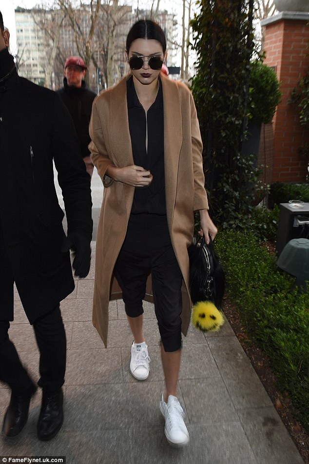 Kendall Jenner kept pace in Milan wearing adidas Originals Stan Smith sneaks, a AYR the Robe Coat in Camel and a One Teaspoon Love Machine Jumpsuit.