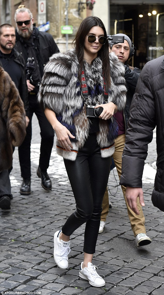 Kendall Jenner took to the streets of Rome, Italy to explore and get her tourist on in Stan Smith sneakers by adidas Originals, JBrand L8007 Edita Leather leggings, and a furry jacket paired expertly with the Asahi Pentax Vintage K1000 camera.