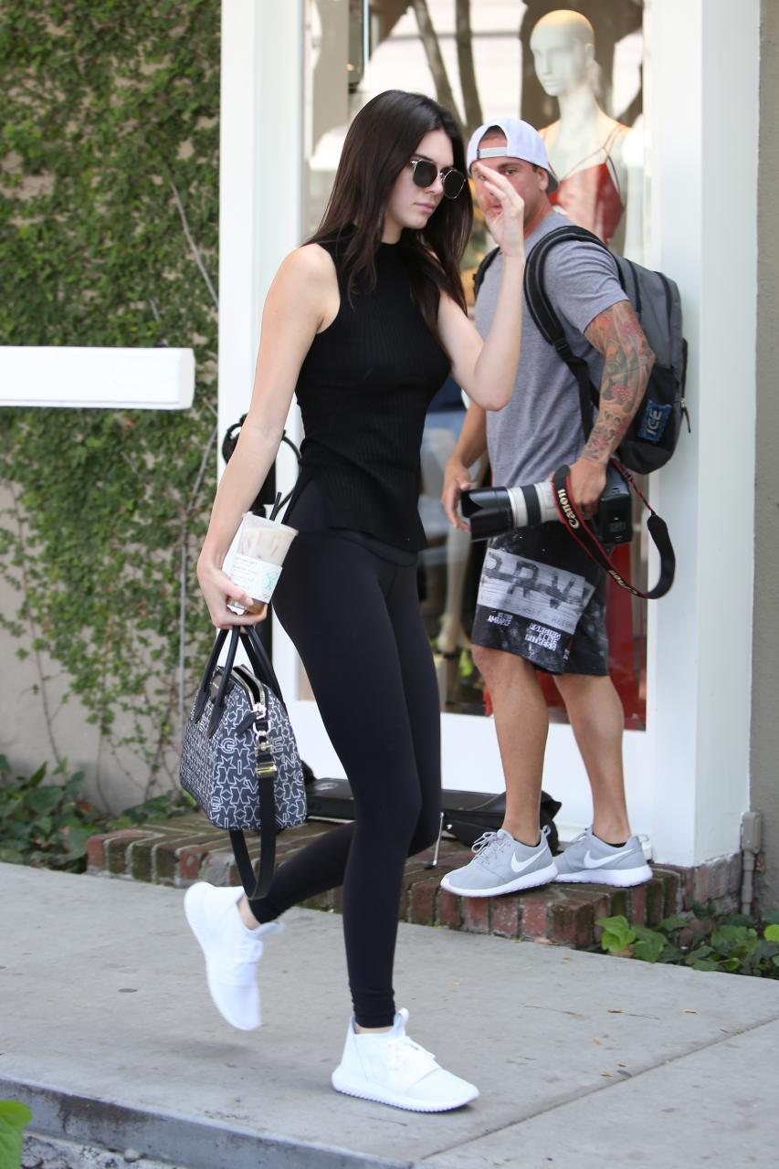 Kendall Jenner was her usual simple style goddess self in wearing Ahlem Eyewear Concorde Sunglasses in Palladium White Gold, Alo Yoga High-Waisted Airbrush Leggings in Black, Adidas Tubular Defiant Sneakers in Core White and an Express Sleeveless Mock Neck Engineered Rib Sweater.