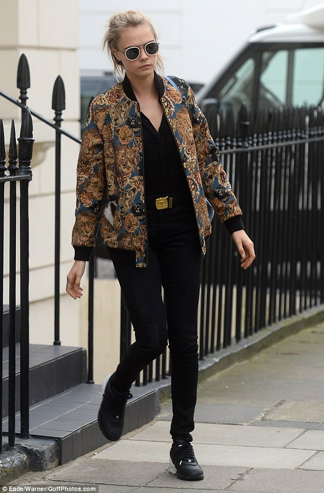 Cara Delevingne took to the streets of London town, pairing her Chanel Calfskin & Neoprene Sneakers with a colorful Saint Laurent Tapestry Teddy Jacket, Perverse Amazeballs Sunglasses and Chanel Black Belt.