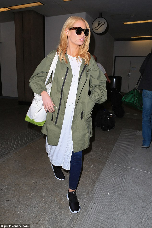 Iggy Azalea had her travel style locked up in an army green jacket and a white shirt dress over blue skinnies and a pair of  Nike Roshe One sneakers.