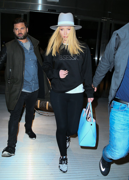 Iggy Azalea made her way through JFK touting a  Dior Addict Shopping Tote , a Calvin Klein Obsession Sweatshirt and a pair of adidas Ultra Boost Reflective Sneakers.