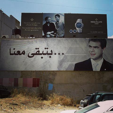 "Photo from Beirut...two billboards, same marketing campaign, different products. The top is a Patek Philippe ad. The bottom is a billboard for the ultra-right wing Kataeb party, showing a martyr next to the words ""You remain with us."""