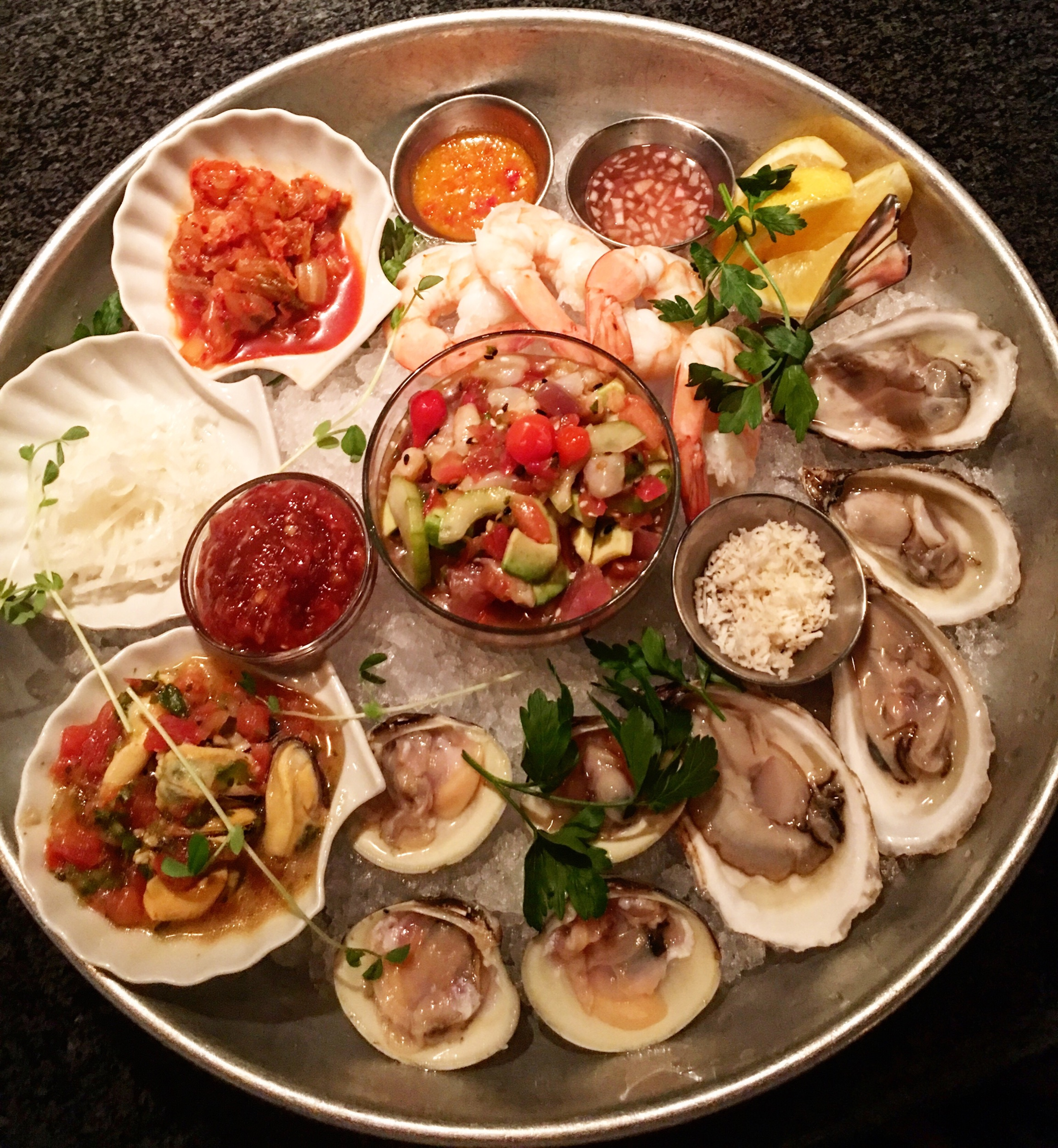 Petit Plateau - iced seafood platter featuring oysters, clams, marinated mussels, shrimp, seafood poke salad, pickled daikon & kimchi.
