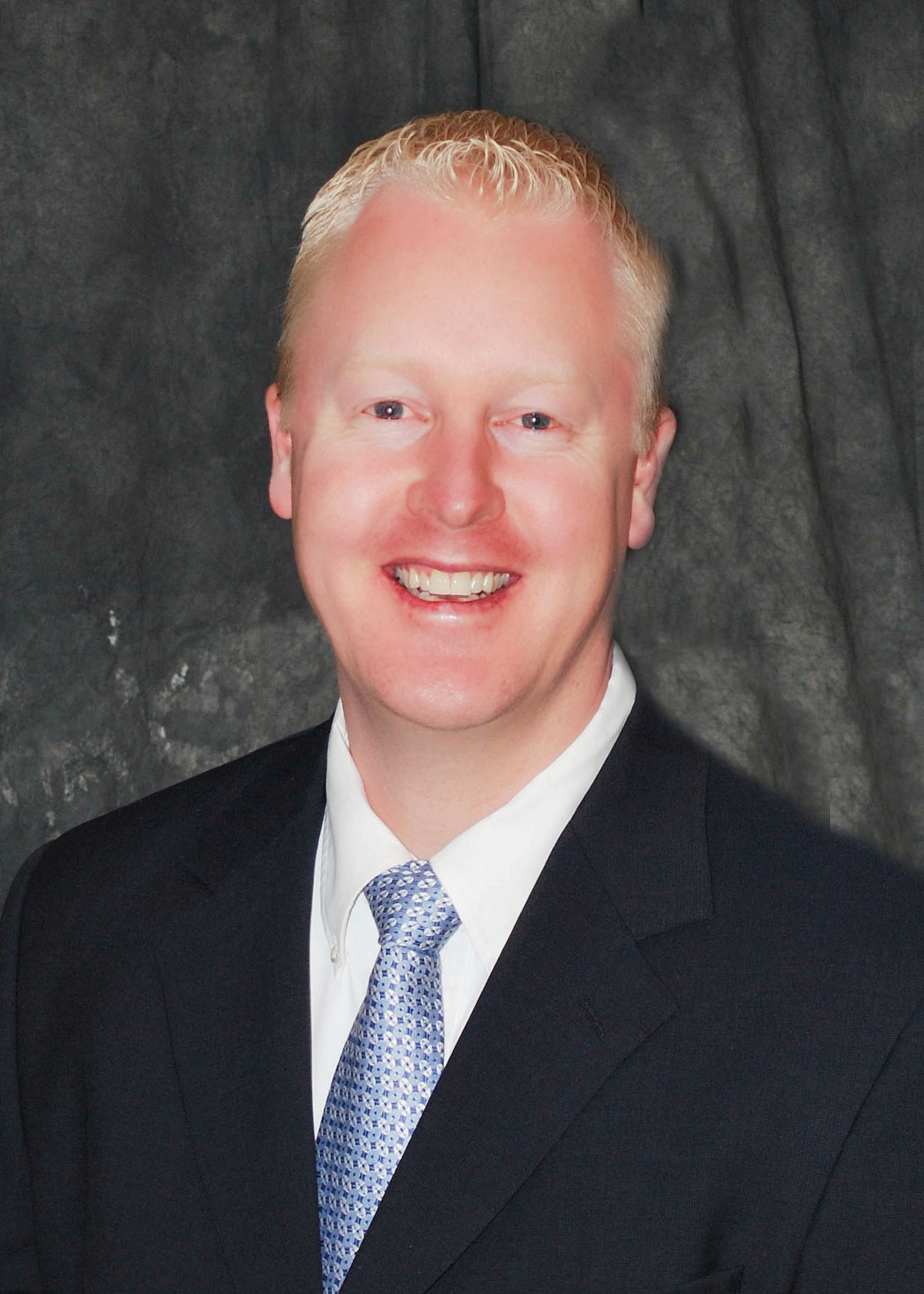 Professional Headshot Photo Of Chiropractor Dr. Steven Davis In A Black Suit With A Blue Tie