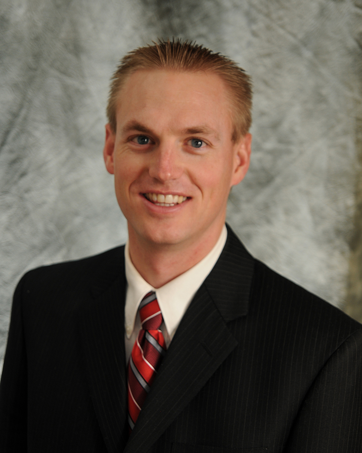 Professional Headshot Photo Of Chiropractor Dr. Brent Wall In A Black Suit With A Red Tie