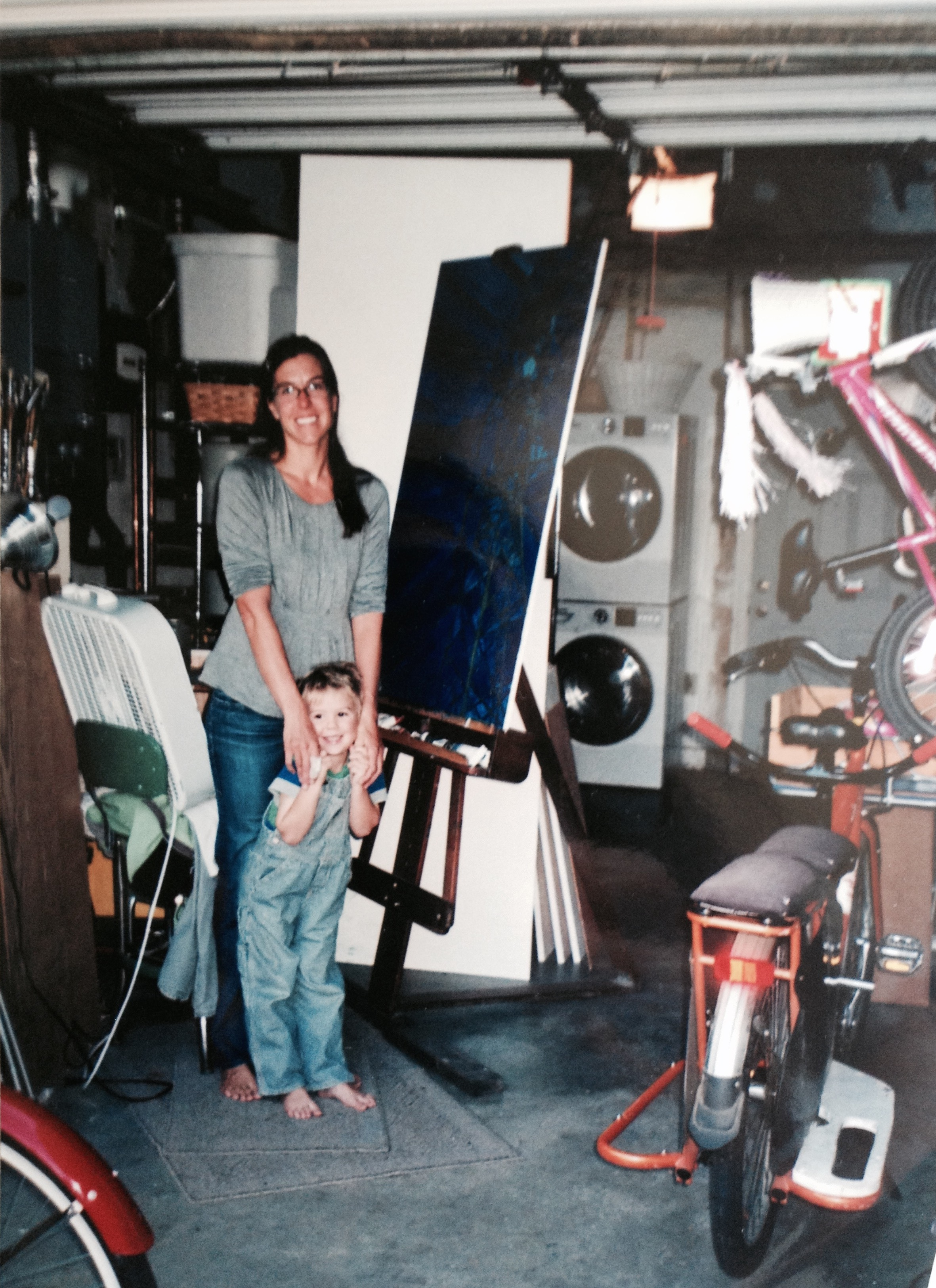 My son and I in my garage studio space, October 2014. Laundry, bikes, and many primed panels await!  (Photo credit: Judith Kays)
