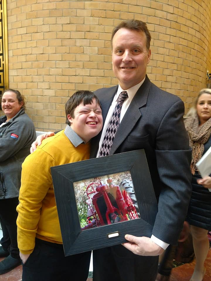 Pictured (L-R): Local resident Tucker Collins with Senator Moore. Tucker presented the Senator with a photograph that they had taken and framed.