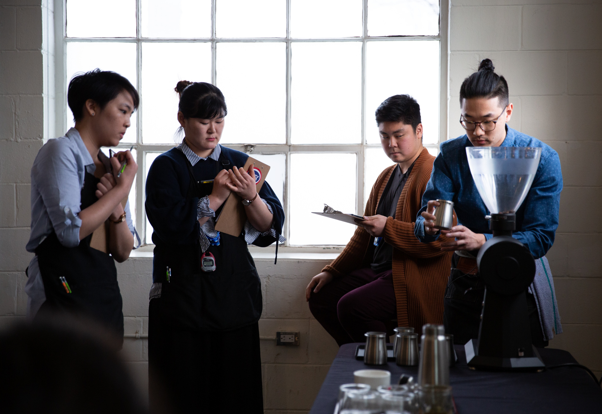 Nelson Phu, 29, from Calgary, grinds coffee beans while judges look on.