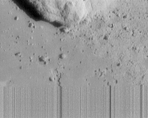 NEAR-Shoemaker was the  first spacecraft to land on an asteroid , which it was not designed to do.  Shown above  is the last picture taken before its touchdown. The streaking on the lower part of the image was caused by the loss of  telemetry  as the satellite impacted the  surface . The image was taken 130 meters above the surface and spans 6 meters across. Rocks as small as a human hand are visible. (NASA/JHU-APL)