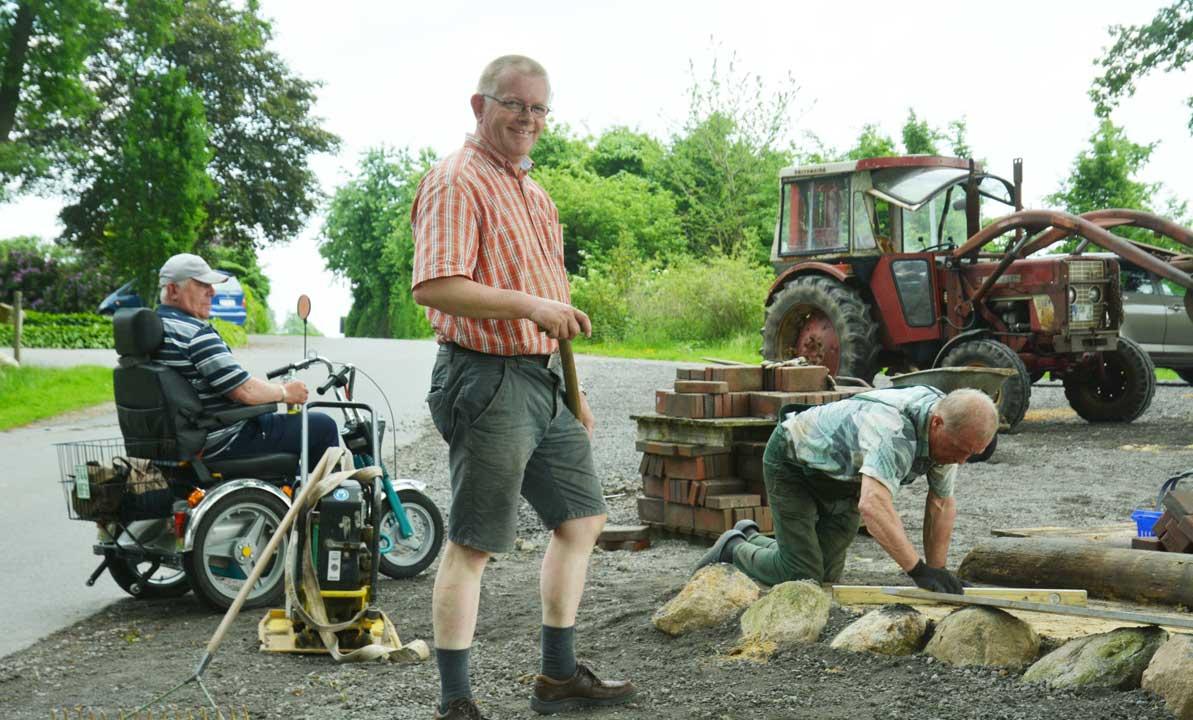 Findlinge stützen die Pflasterung an dem abschüssigen Gelände an der Hütte in der Krevinghausener Schweiz.