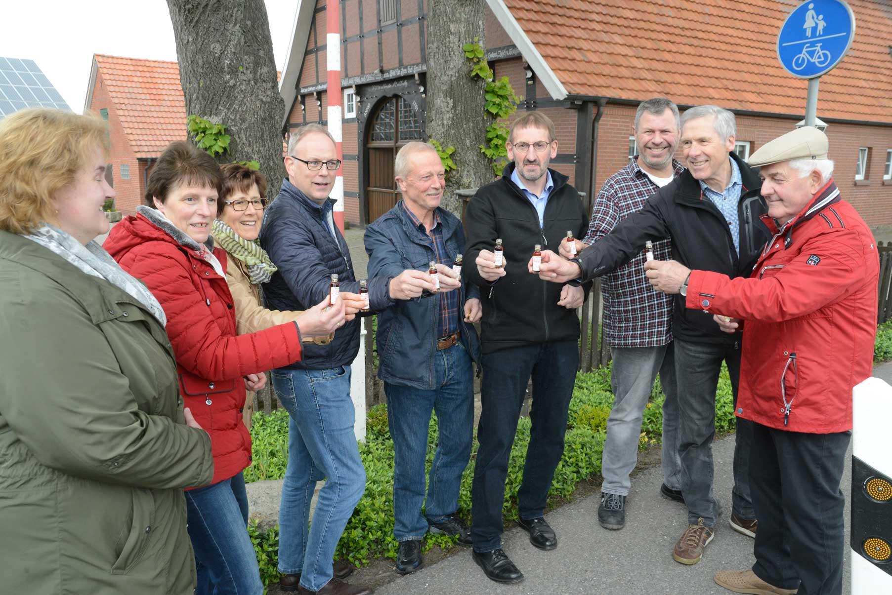 """Auf die gelungene Restaurierung stießender Heimatverein mit Gastwirt Dobelmann und Bürgermeister Frerker mit einem """"Zaollbaum-Tröpfen an."""