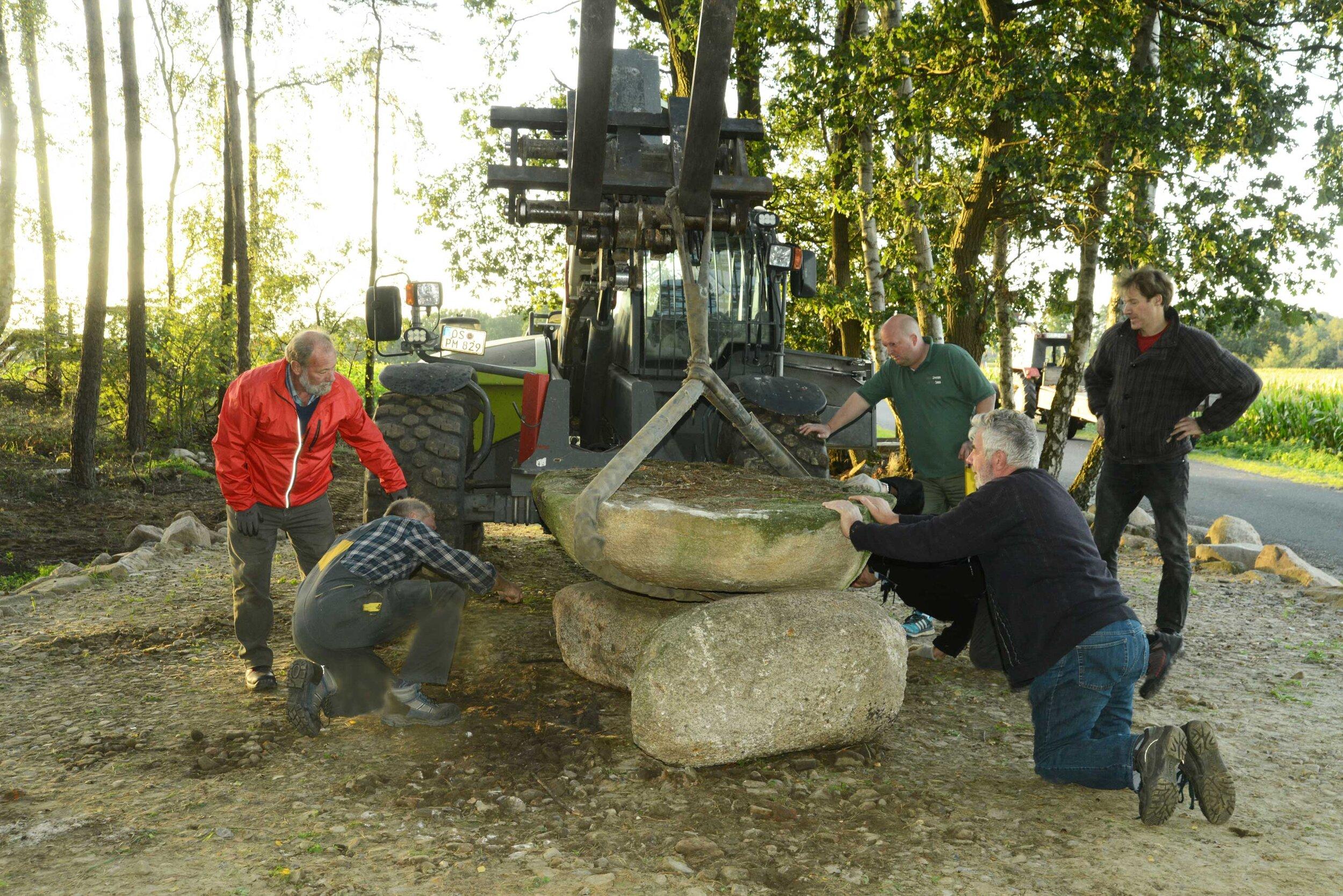 """Mit Hilfe von schwerem Gerät wurde die steinerne """"Tischplatte"""" auf dem Steinplateau platziert."""