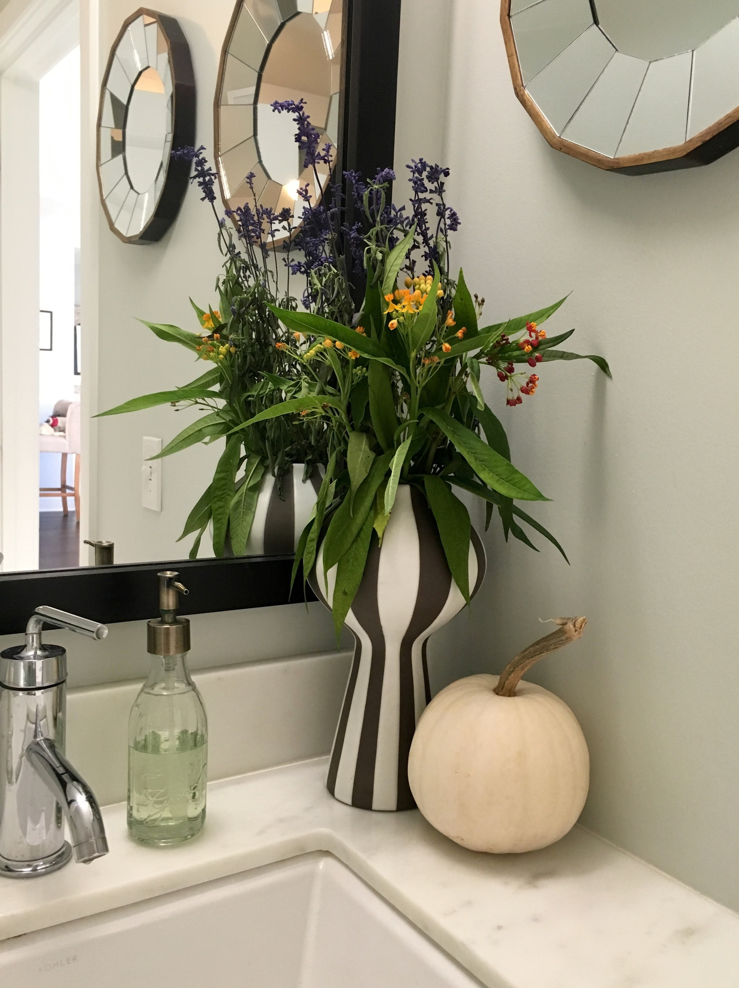 Rustic flowers and pumpkins in the guest bath.