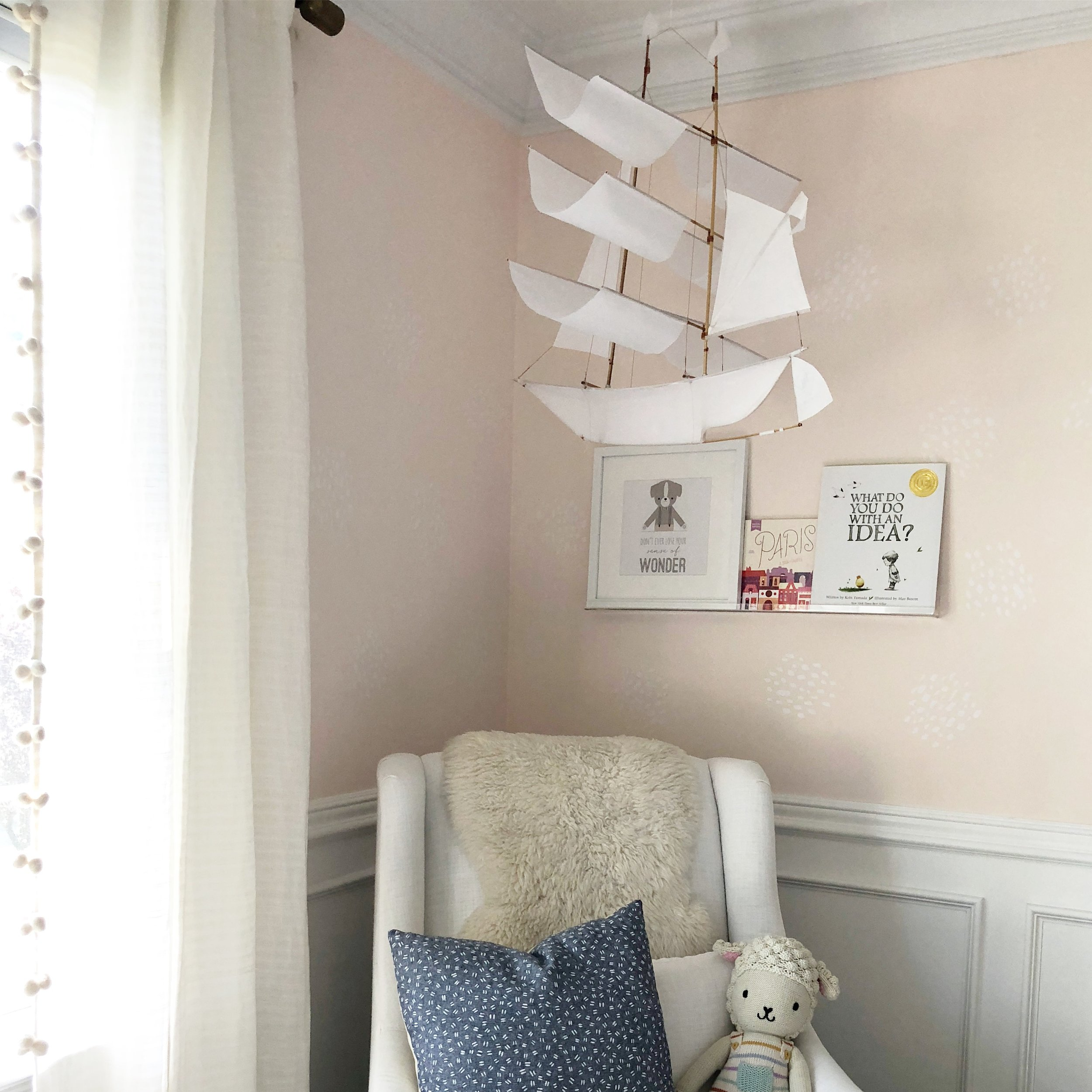 To cozy up this corner, I hung this white sailboat kite (yep, a real kite!). It's neutral and whimsical and I like that it's a unique alternative to a traditional mobile.