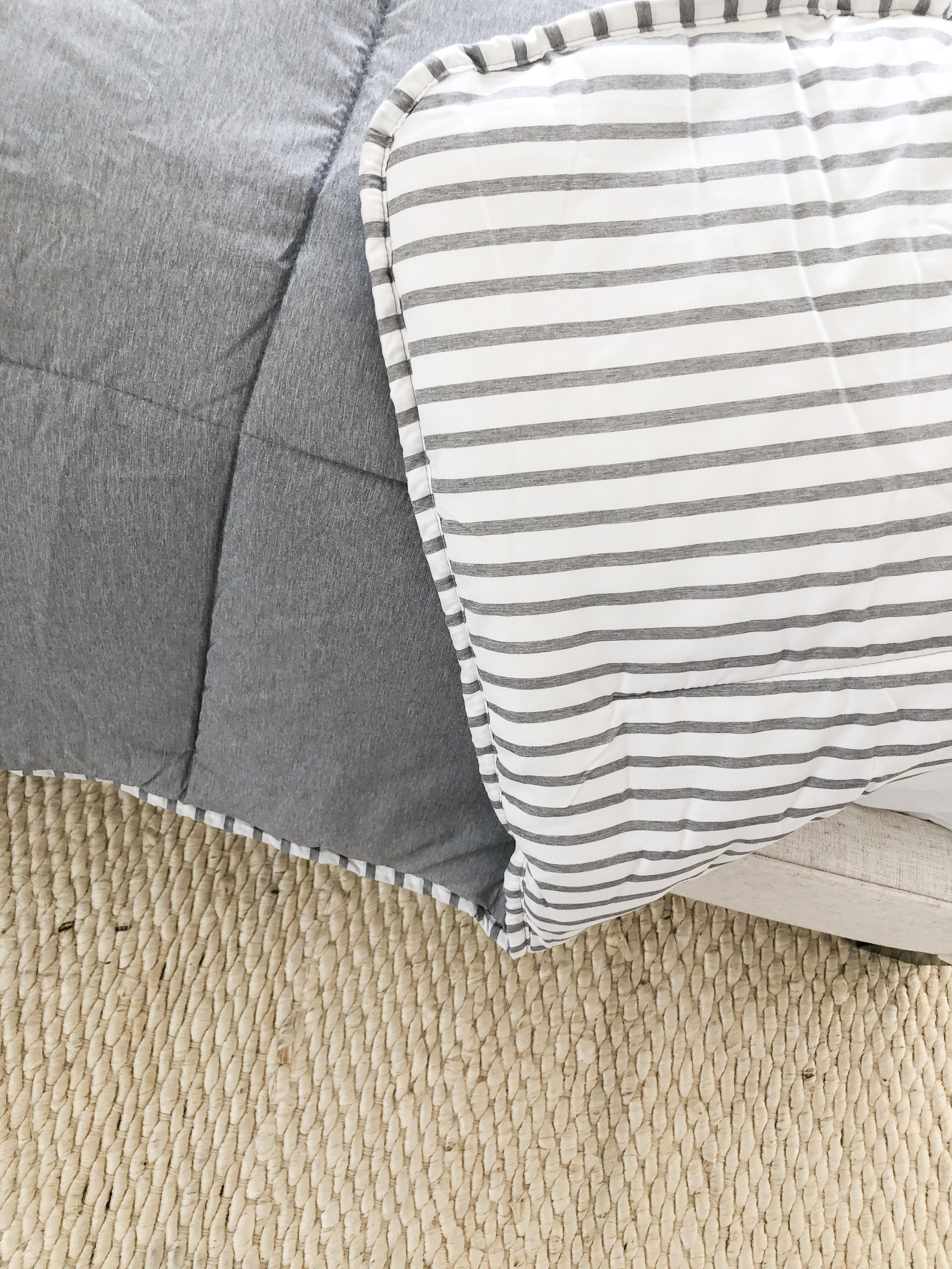 A close-up of the reversible chambray quilt I chose. One side is a blue/gray chambray and the other side is gray and white striped. Super lightweight and perfect for layering onto a bed.