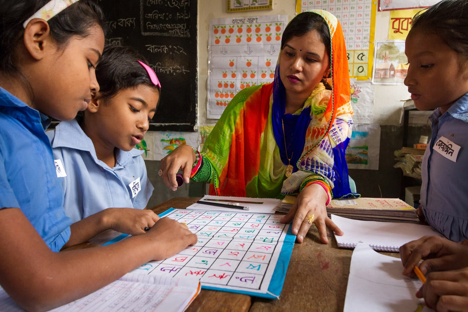 """Shushmita and other classmates play a board game designed by her teacher, Ayesha Parveen. The game is designed to help them recognize the 51 letters that make up the Bangla alphabet and learn the sounds each represents. """"After playing for a few months, they started to recognize the letters,"""" Ayesha says. """"Now Shushmita can recognise all of them and read without my help."""" Shushmita is one of the lucky ones. In many if not most schools in Bangladesh her teacher would never have even recognized the problem. But in Uttar Kafrul Government primary school, the teachers have all had training in UNICEF's Each Child Learns (ECL) programme. Built into the approach are methods through which teachers ensure the continuous assessment of each student's performance and work with them creatively as individuals, even in the school's over-crowded classrooms."""