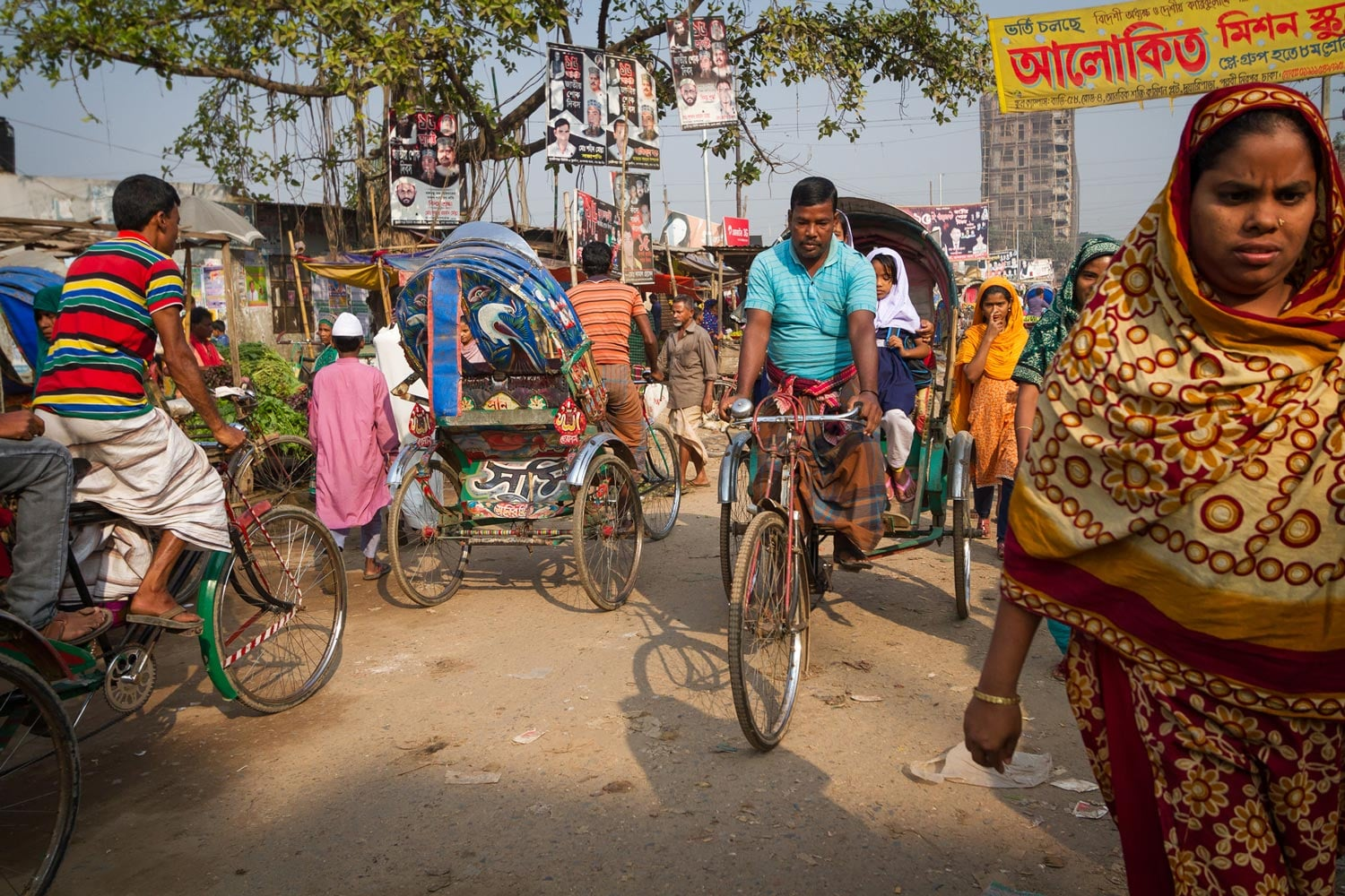 """Azharul Islam (in blue shirt) takes Moni and Aduri to school on his rickshaw. """"I am very concerned about my daughters,"""" he says. """"It is my responsibility to keep them safe in this environment."""""""