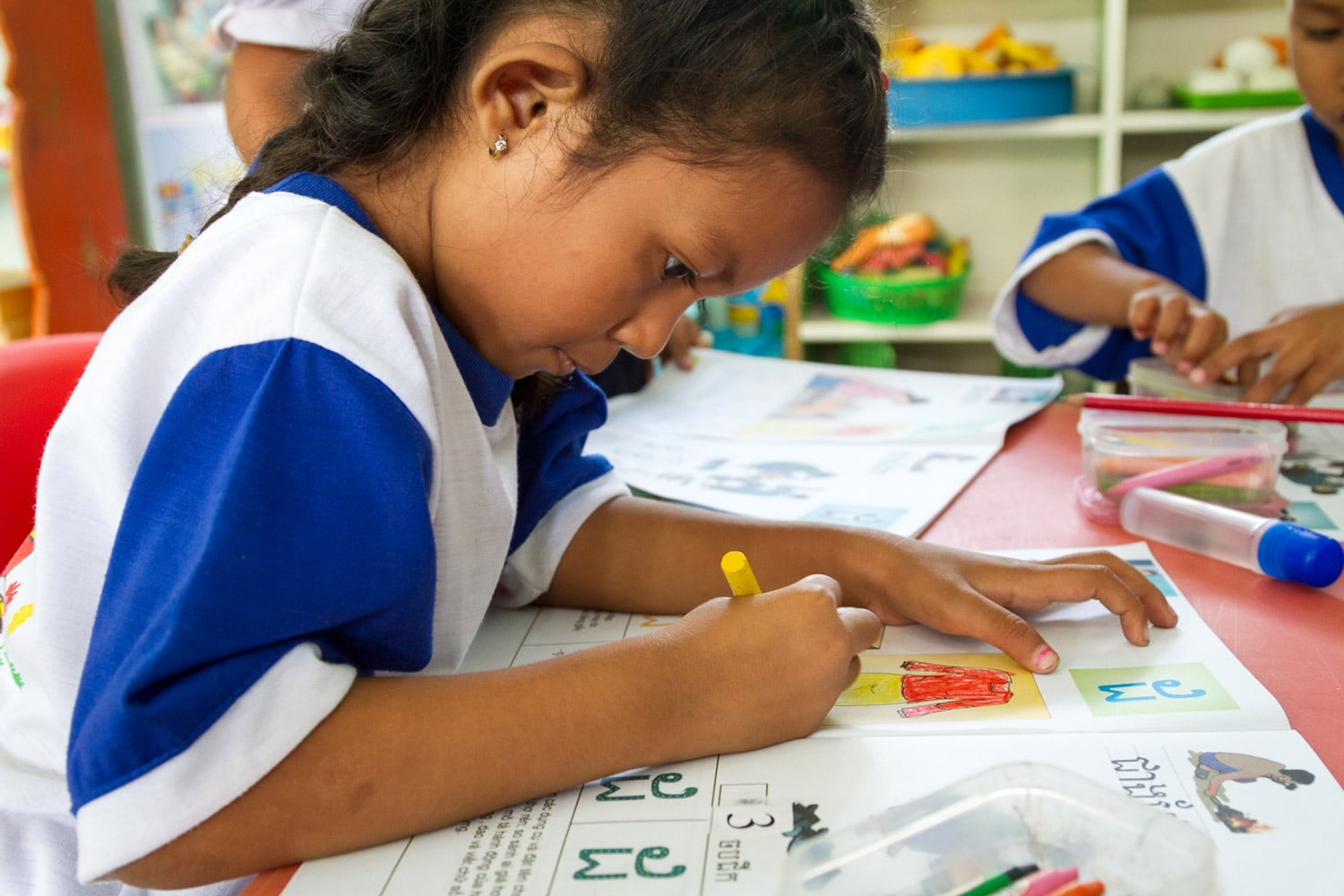 Ngoc colours in a UNICEF-supported workbook that features Khmer letters and culture.