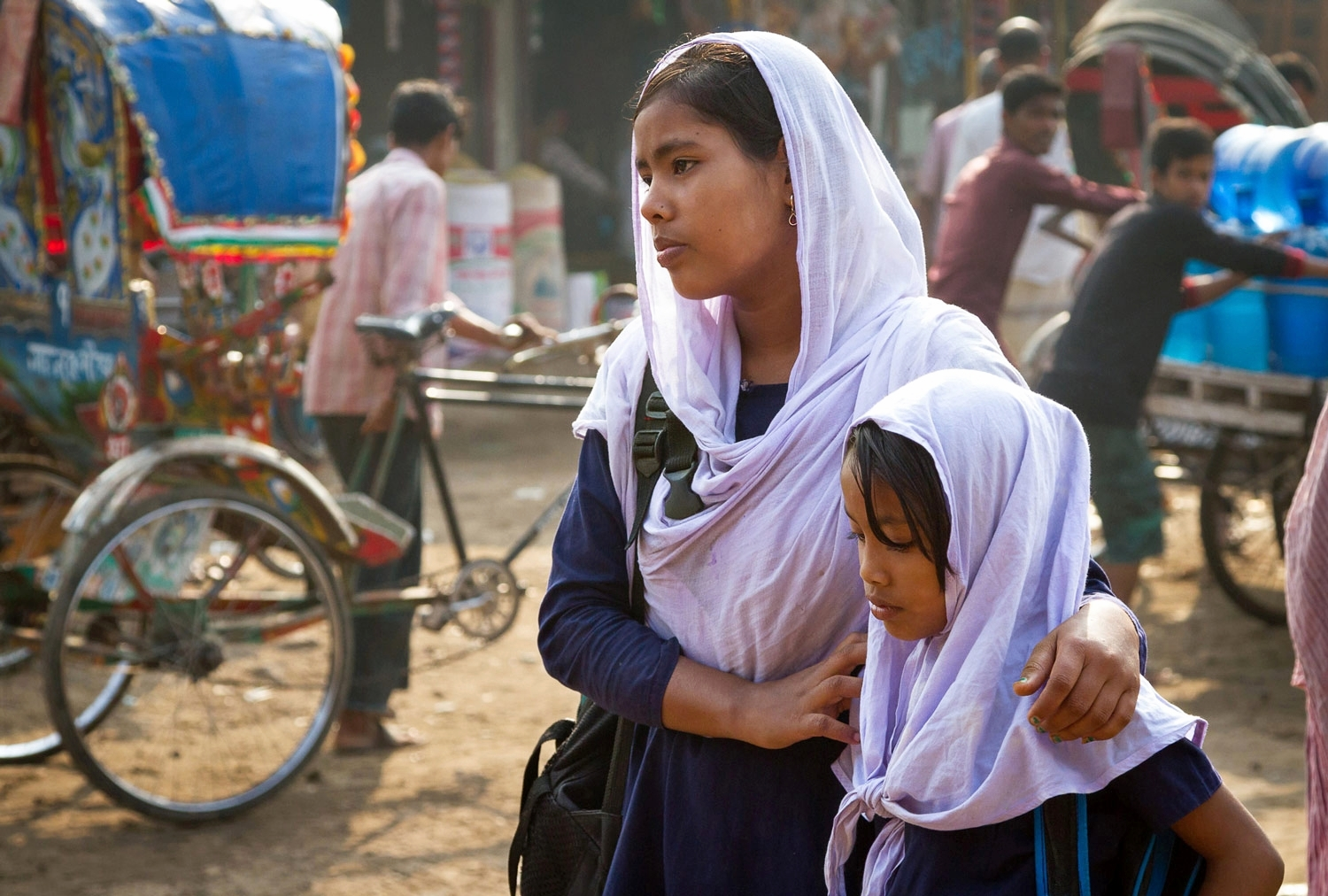 Two sisters await a rickshaw to take them to school; Duaripara slum, Dhaka, Bangladesh