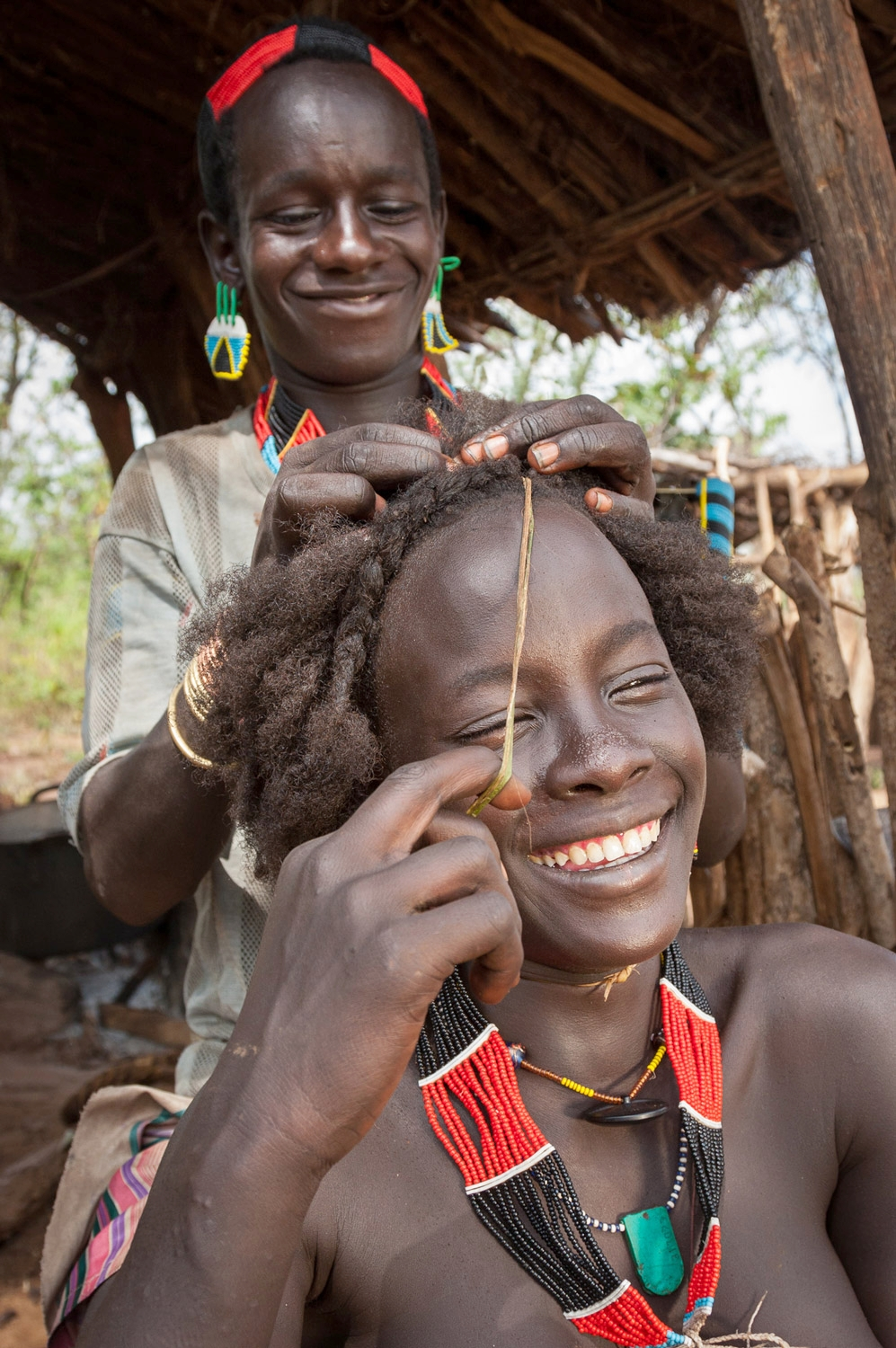 Bito fixes Bona's hair; Omo Valley, Ethiopia