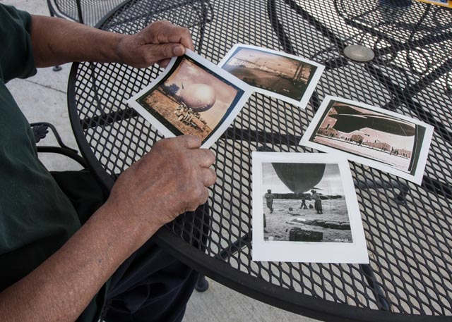 Sam Mattison flips through photos of the barrage balloons that he flew in Tennessee, Britain and on Omaha Beach.   Photo: Linda Hervieux