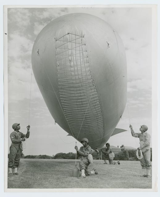 Four men from a black barrage balloon unit hoist aloft a balloon during a 1942 demonstration in Washington, D.C. Elasticized ropes allowed the envelope to expand as the balloon went up and the gas inside expanded.  Photographer: Roger Smith; Photographs and Prints Division, Schomburg Center for Research in Black Culture, the New York Public Library, Astor, Lenox and Tilden Foundations