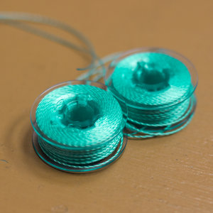 Size L bobbins wound with 12wt Accent™ thread