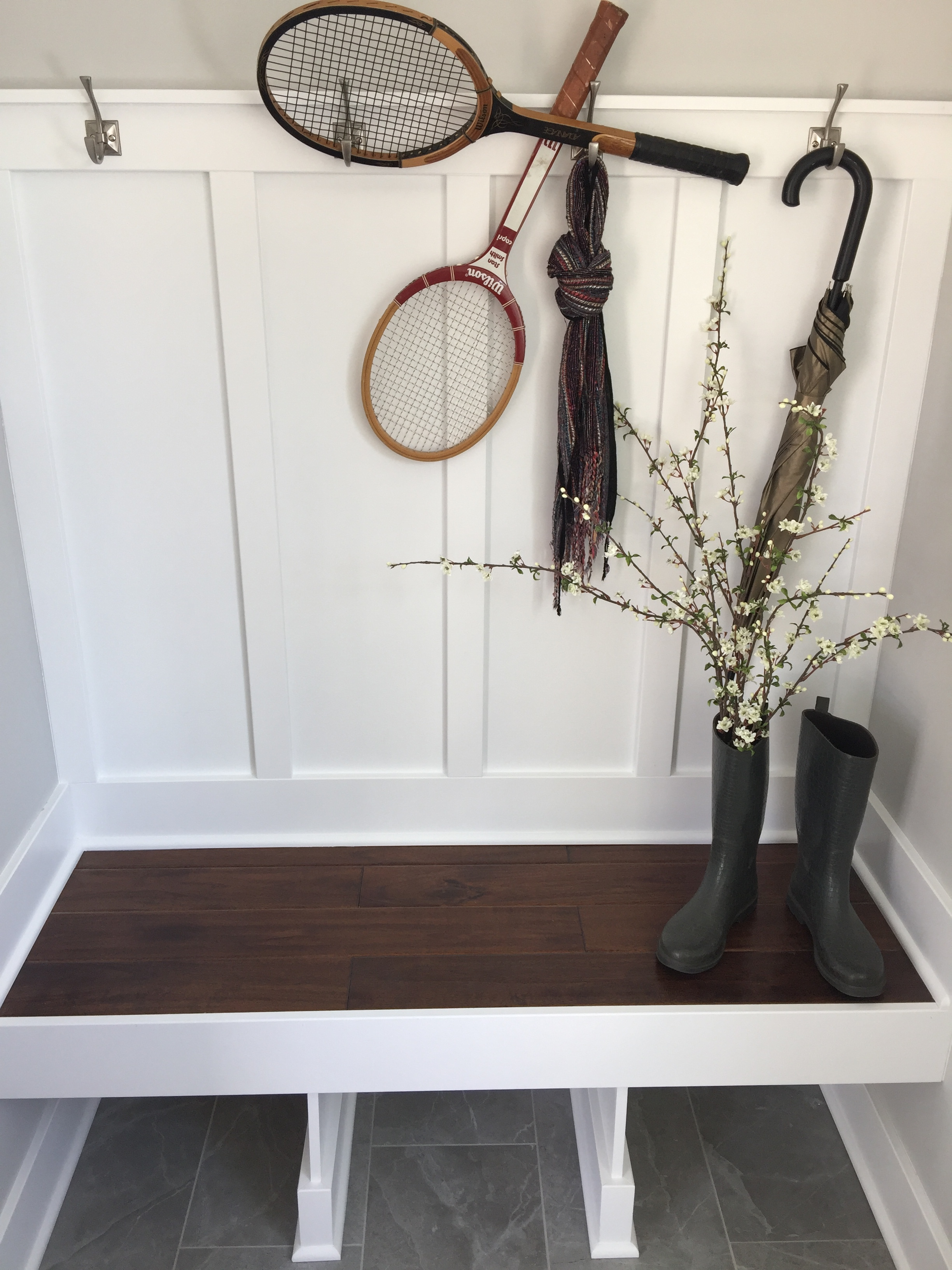 custom built mudroom bench with wood seat and white enameled back and hooks.