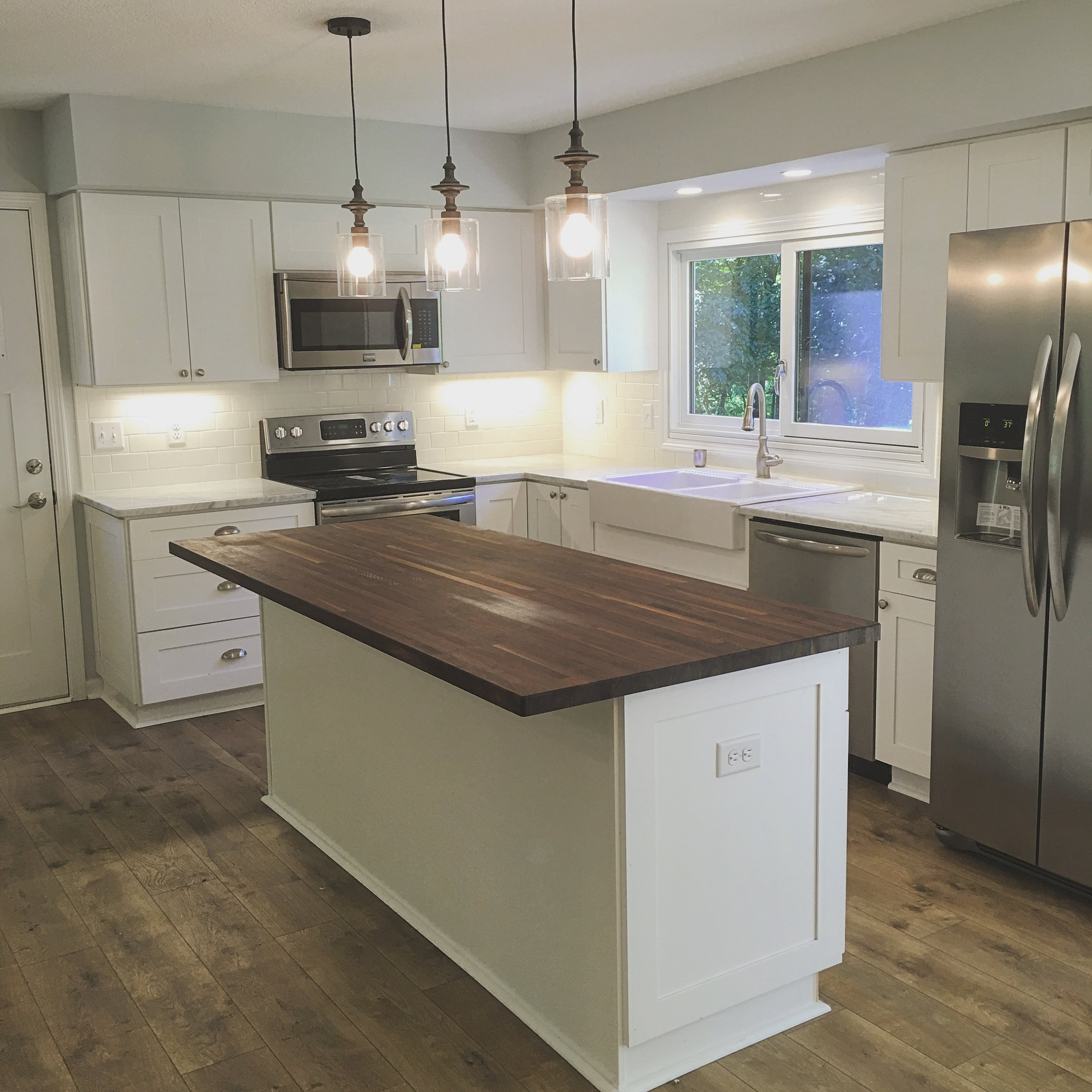 Rustic kitchen with marble countertops, walnut butcher block, laminate flooring, and farmhouse sink. Before and after of home remodel in Minnesota