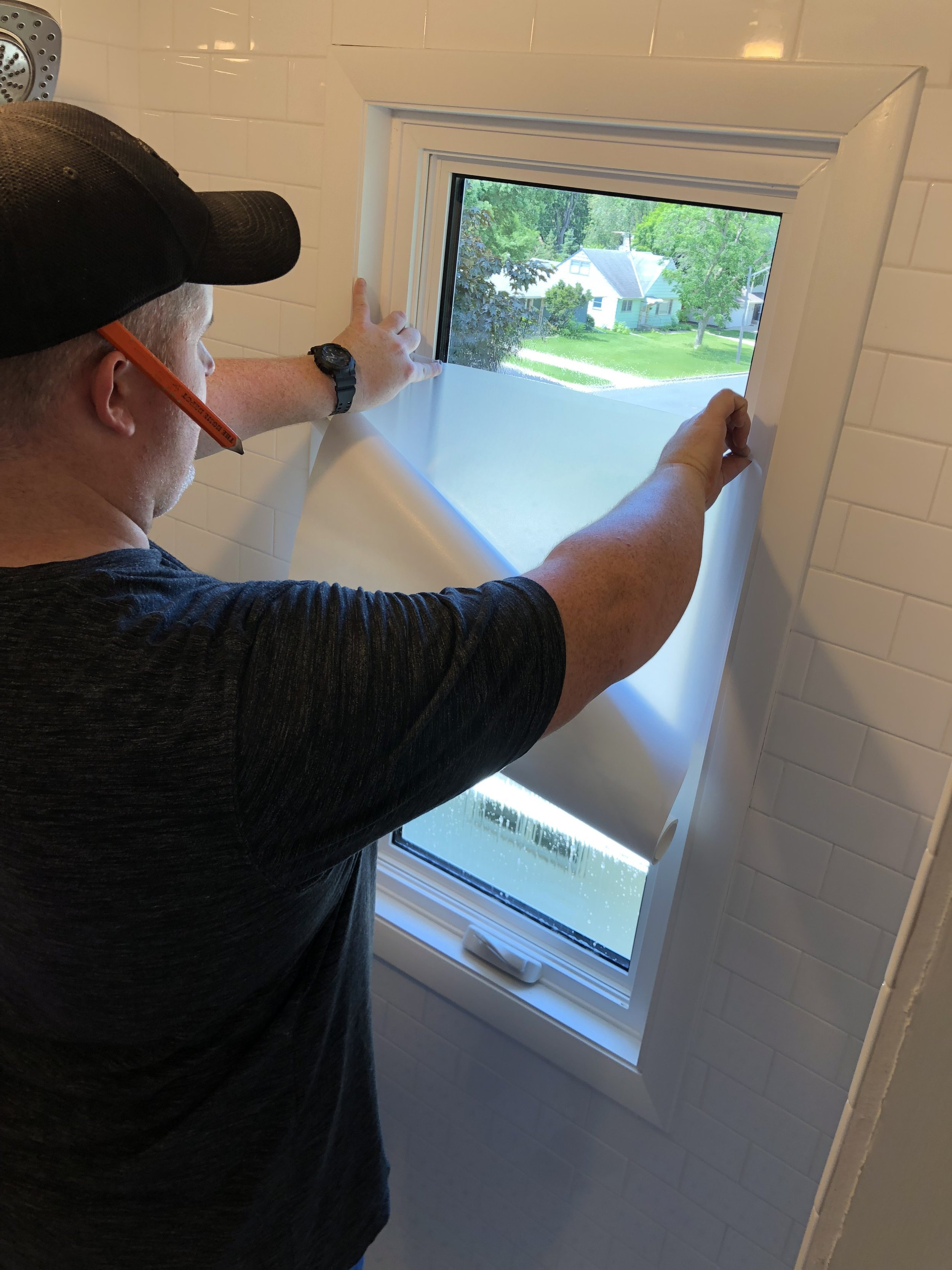 Window with privacy film being applied