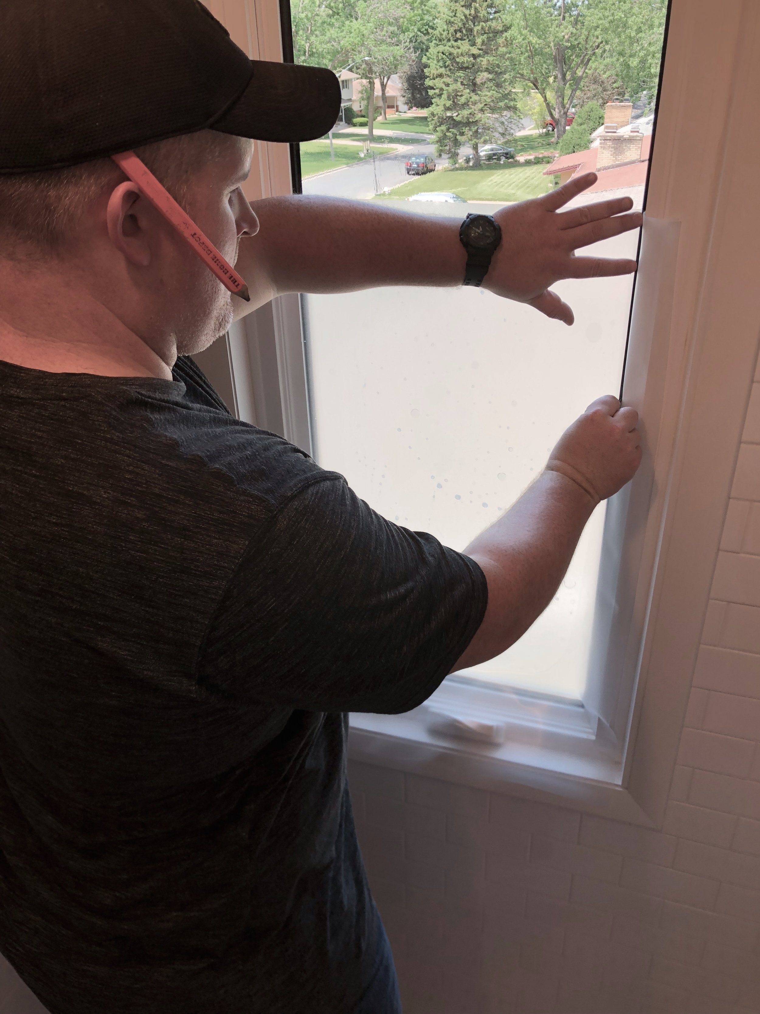 Cut off excess privacy film around edge of window