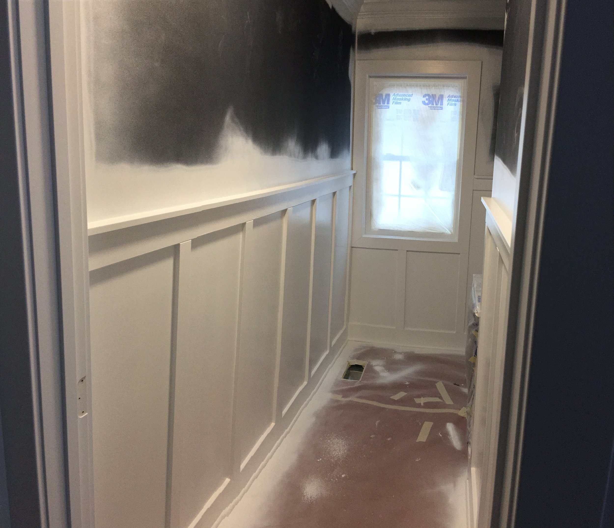 White enamel paint applied to wainscoting in powder bathroom with paint sprayer