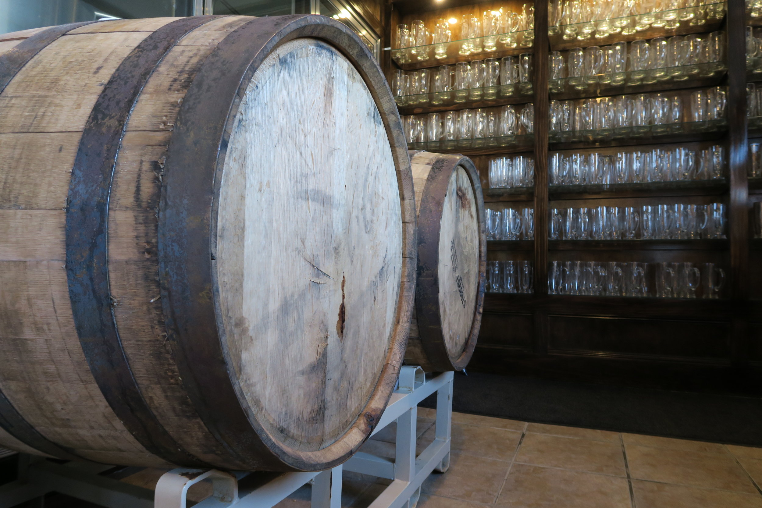 Beer aging in bourbon barrels in front of the mug club wall