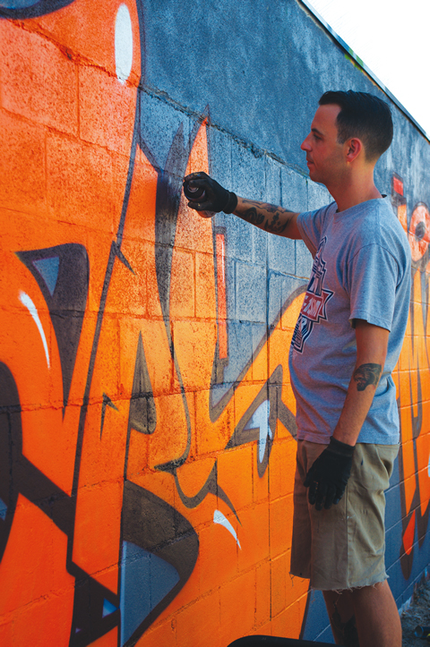 Australian artist Dabs paints a wall behind Costa Mesa's Mesa Art. Photo by Linda Domingo