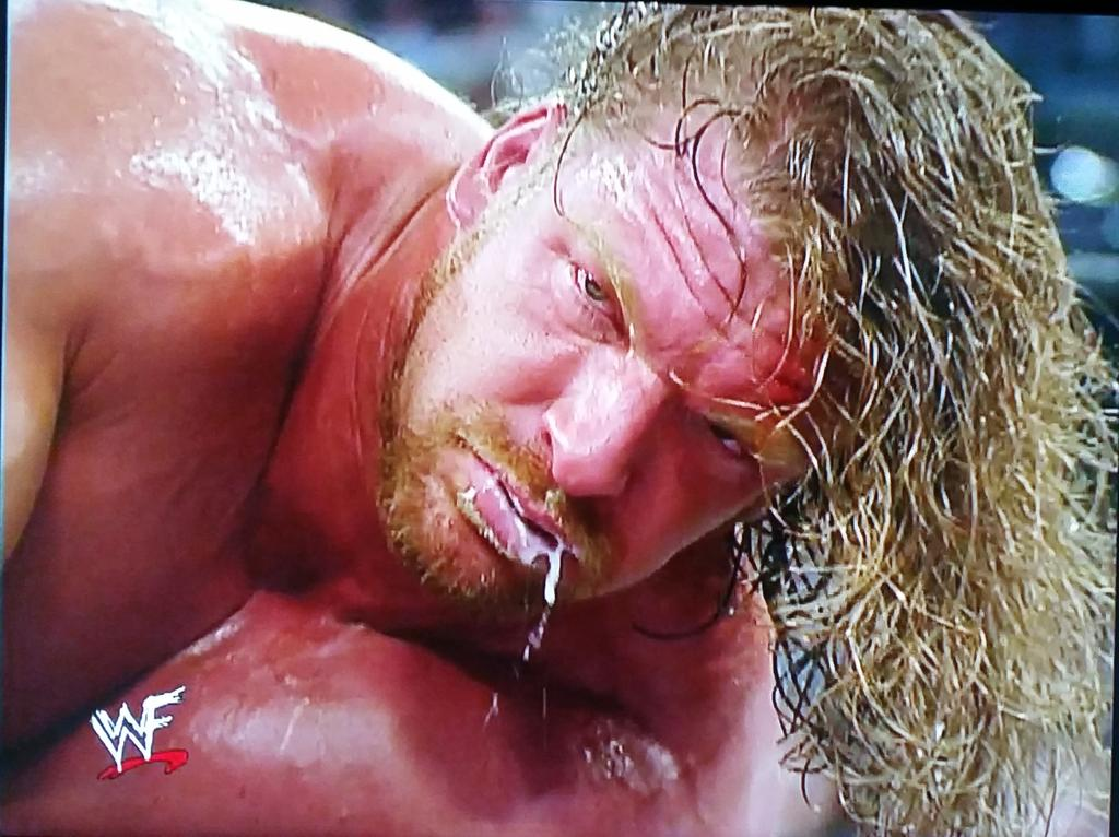 Gross HHH playing Yo-Yo with his spit after losing to Kurt Angle