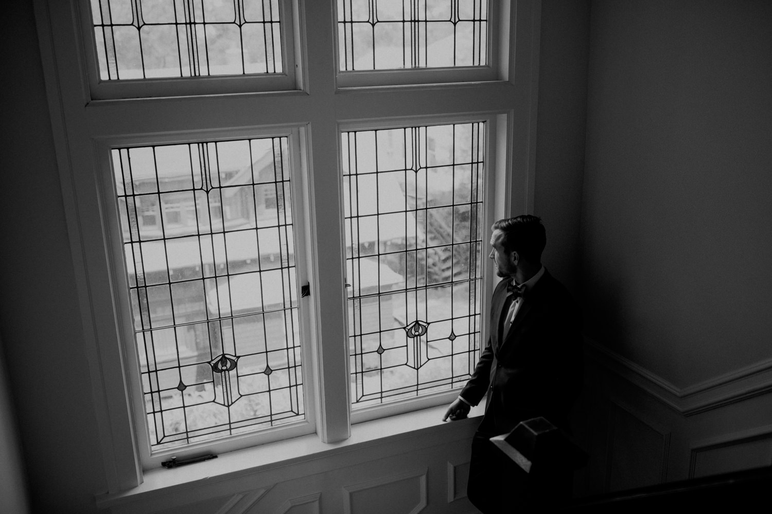 The groom looks out the window from the Craigmyle Bed and Breakfast.