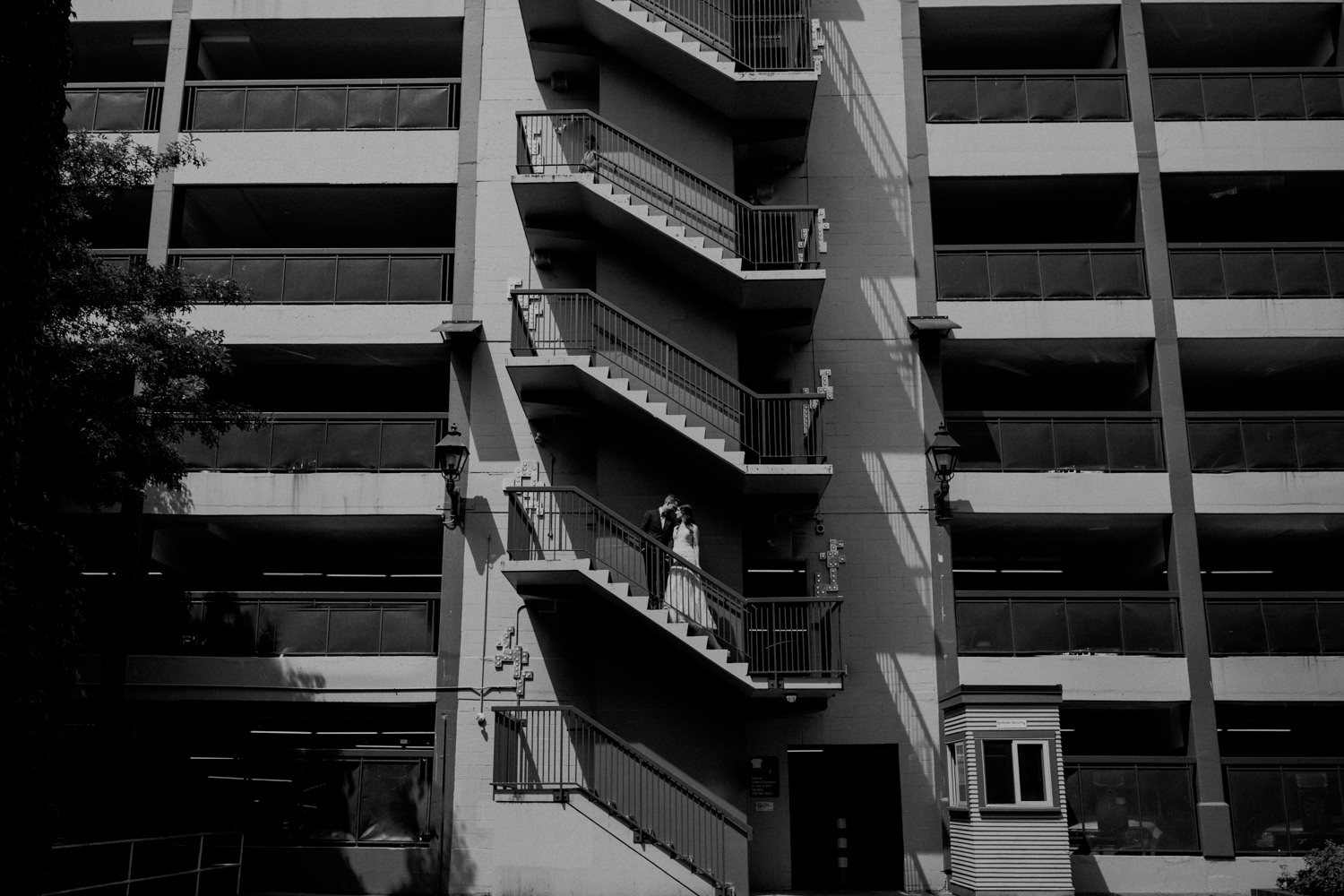 The bride and groom share a moment on the staircase of a parkade in downtown Victoria. Photographed by Candice Marie Photography.