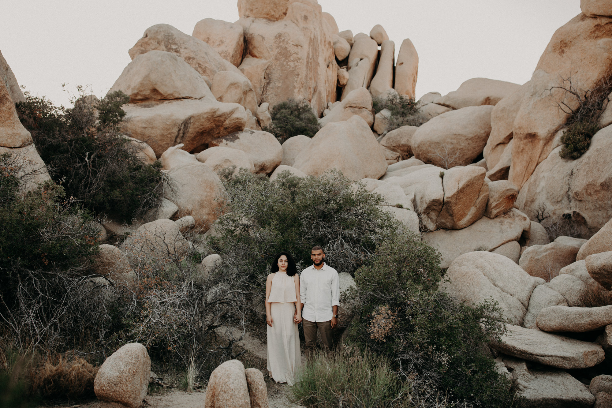 An engaged couple holding hands, perfectly centred in the boulders of Joshua Tree Park.