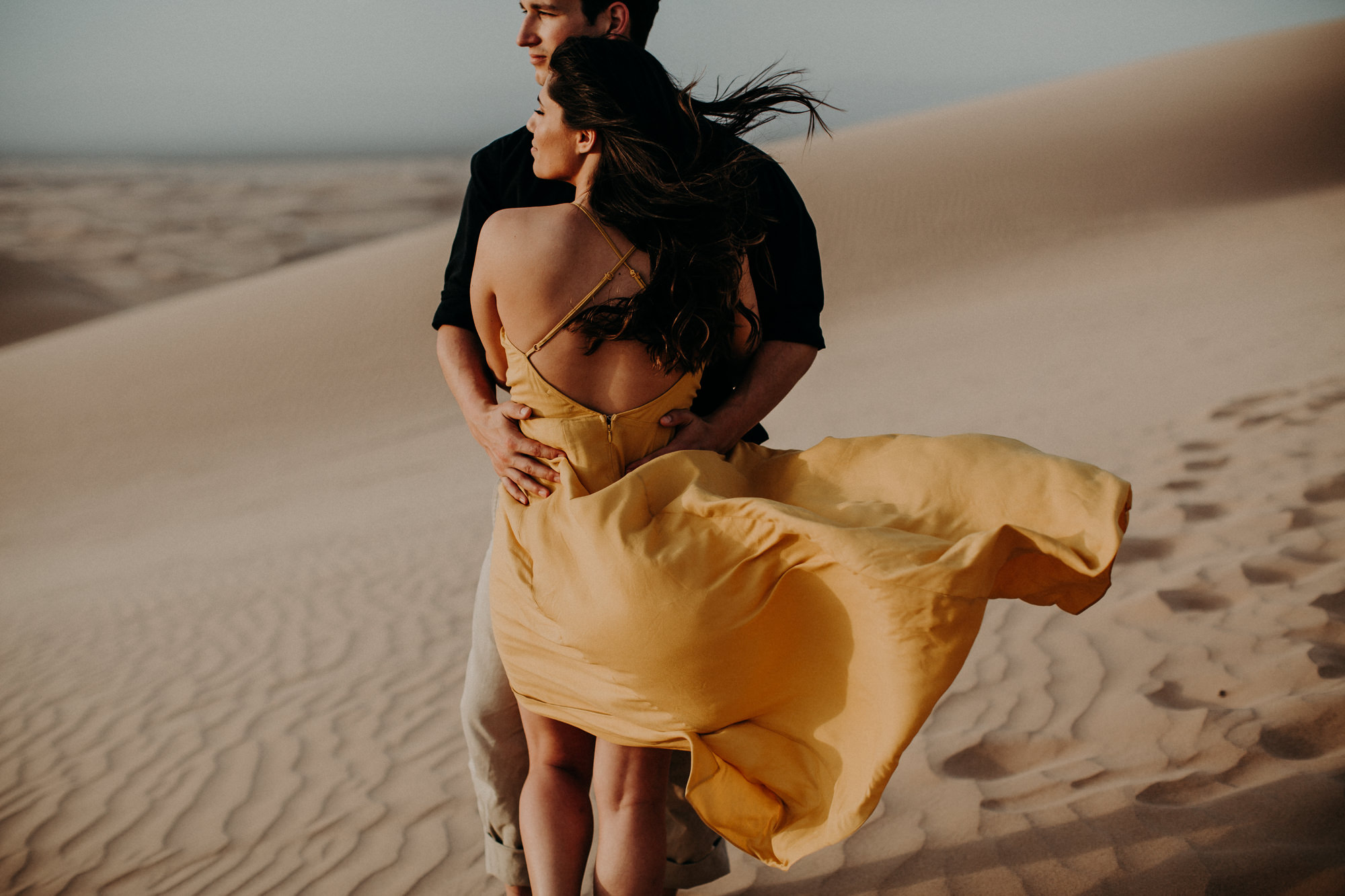 A couple hugging as the wind blows through her yellow dress, at the glamis imperial sand dunes near Palm Springs. Photographed by Candice Marie Photography.