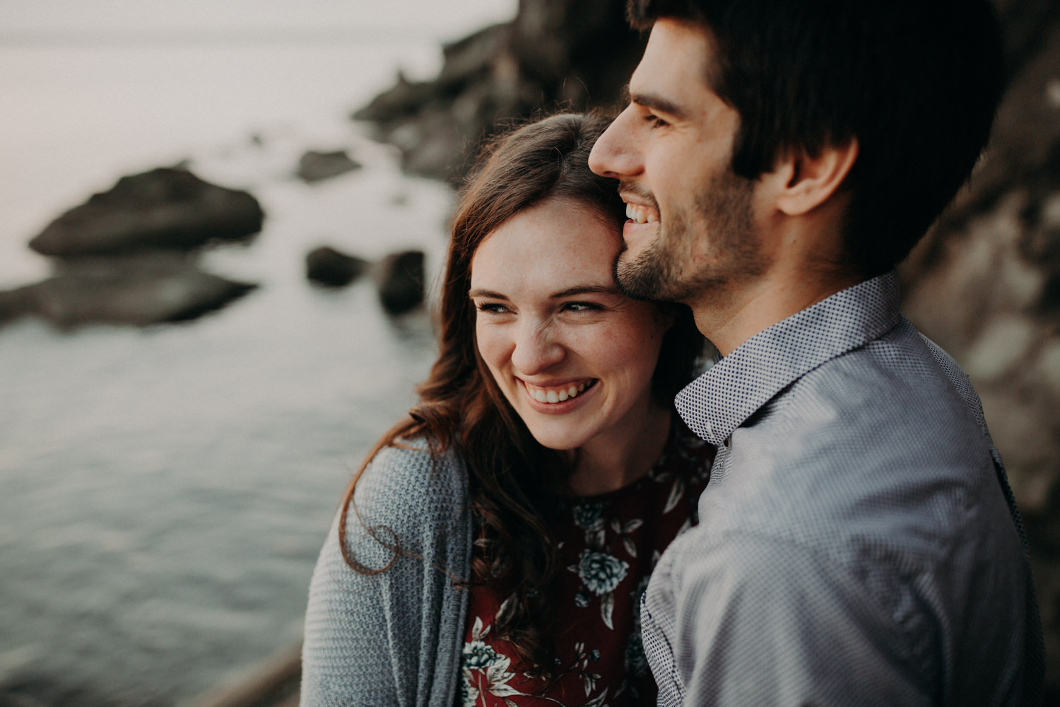A photograph of an engaged couple embracing at Clark's Point in Bellingham, WA.