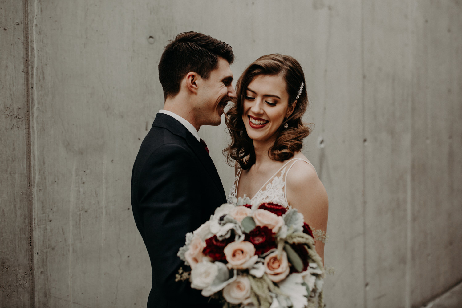 A candid photograph of a happy couple at the parking garage on the campus of SAIT; the groom whispers something sweet into the brides ear and she is smiling.